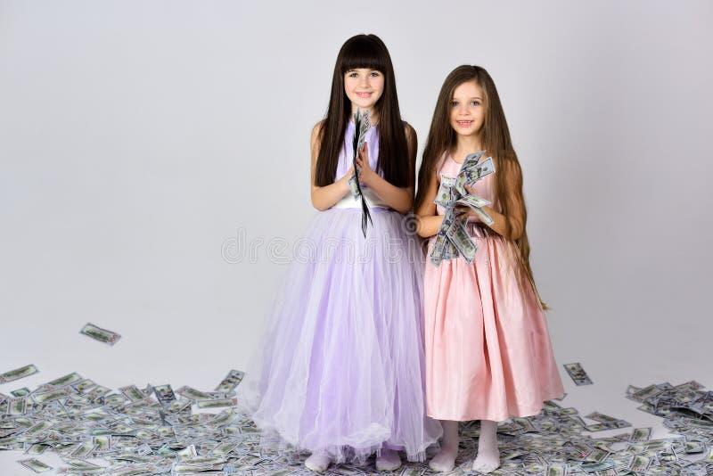 hermanas con el dinero, dólares, ahorros de las niñas imagen de archivo