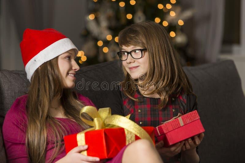 Hermanas con los regalos de Navidad que miran uno a en el sofá fotos de archivo libres de regalías