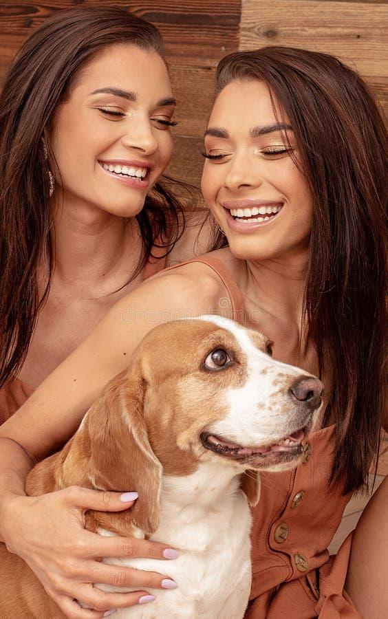 Hermanas de los gemelos que juegan con el perro lindo, sonriendo imágenes de archivo libres de regalías