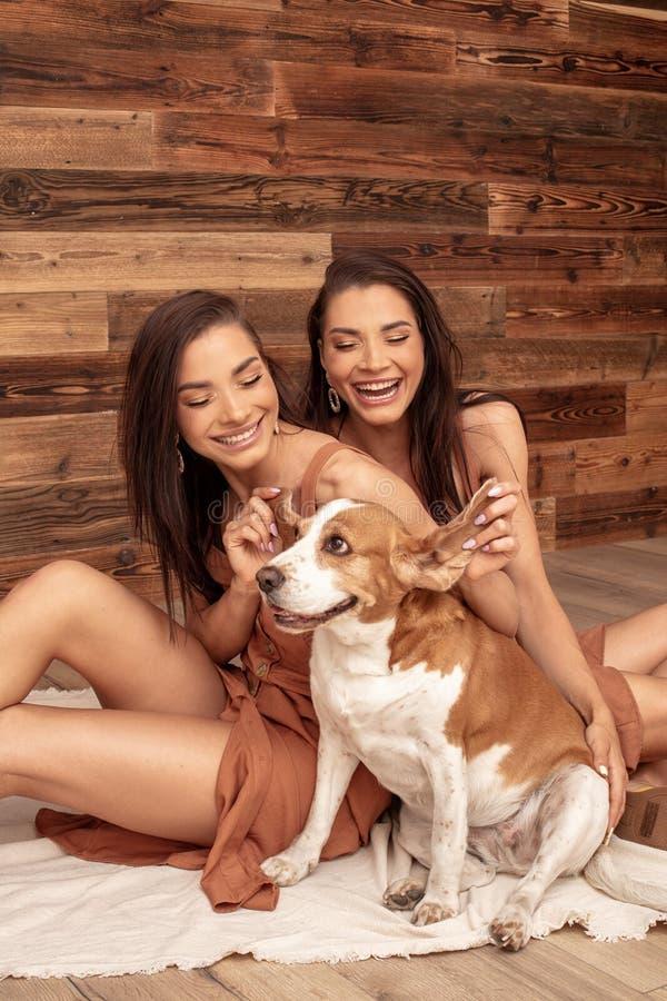 Hermanas de los gemelos que juegan con el perro lindo, sonriendo imagenes de archivo