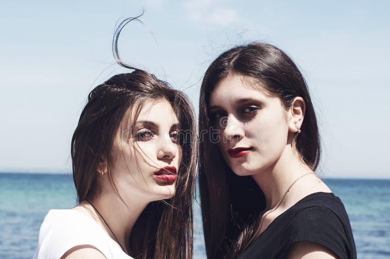 Hermanas en la playa que se abraza Retrato de jóvenes hermosos imagenes de archivo
