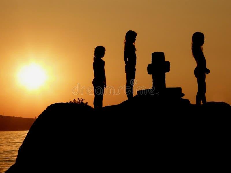 Hermanas en rezo en puesta del sol foto de archivo