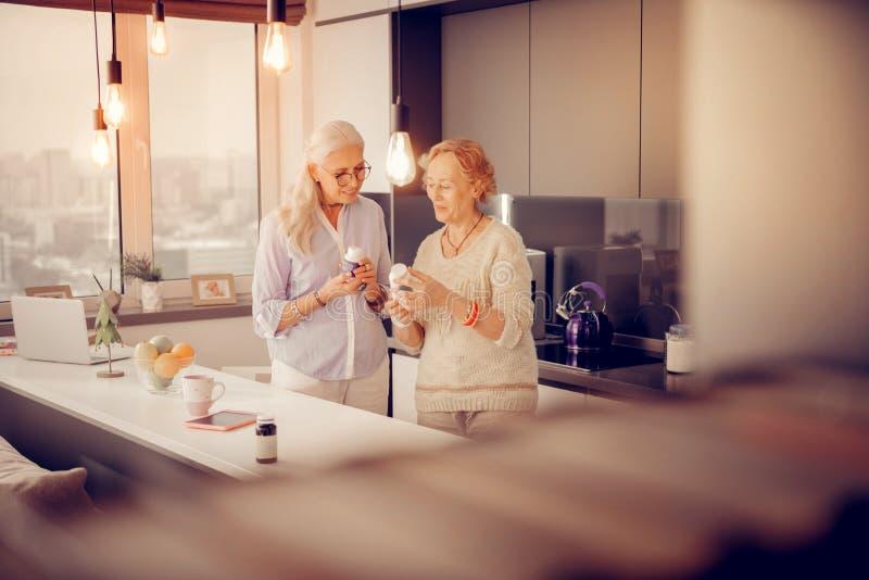 Hermanas envejecidas agradables alegres que hablan sobre salud foto de archivo