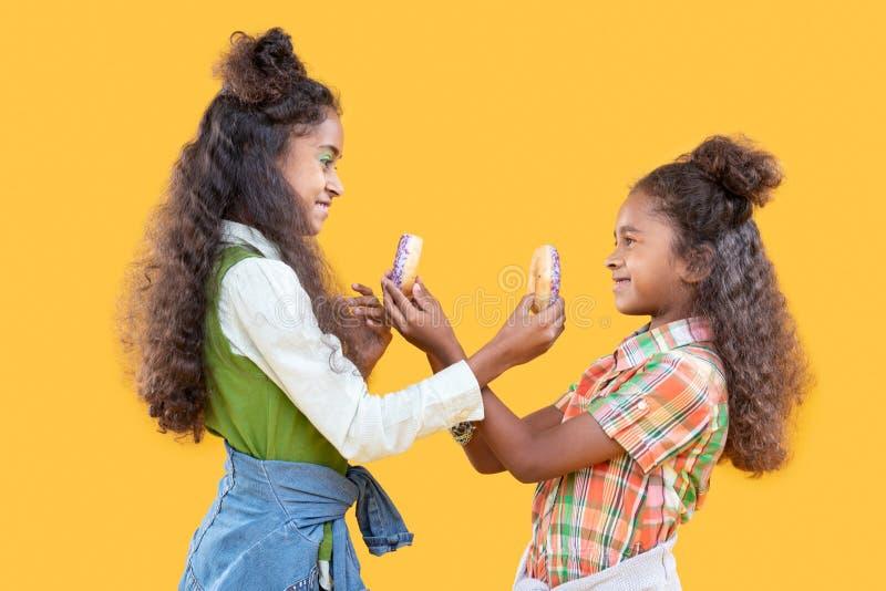 Hermanas felices alegres que se muestran los anillos de espuma fotografía de archivo libre de regalías