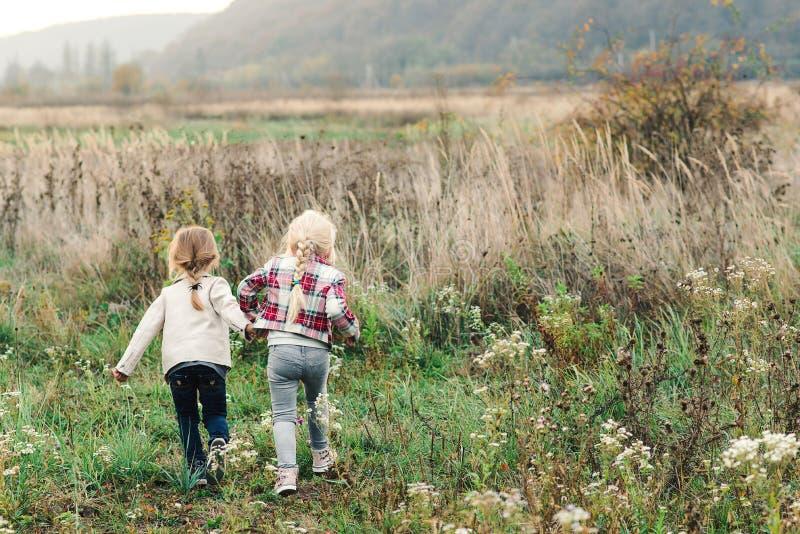 Hermanas felices corriendo en un campo el día del otoño Concepto de amistad, infancia, ocio y personas Dos niñitas corriendo fotografía de archivo