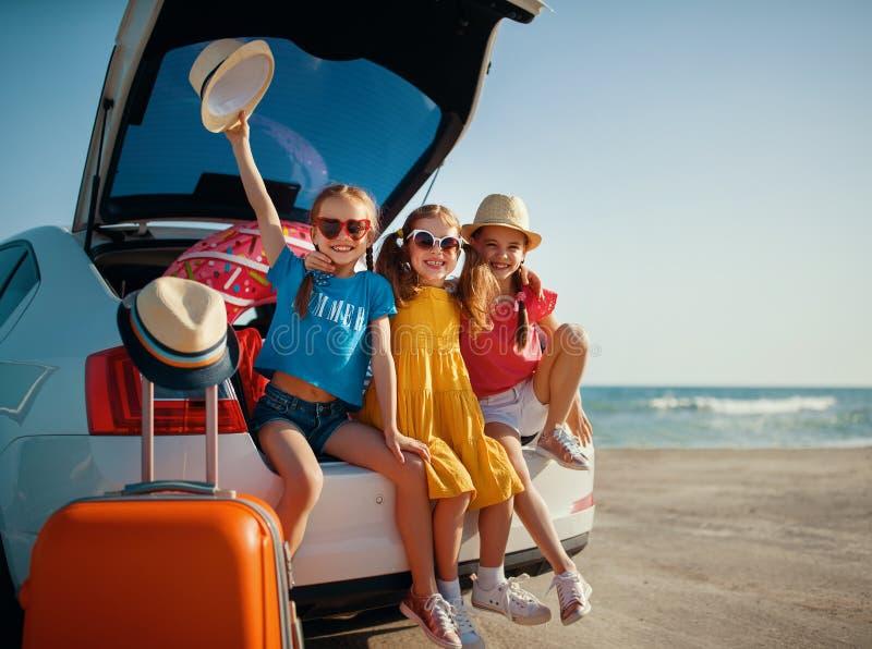 Hermanas felices de los amigos de muchachas de los ni?os en el paseo del coche al viaje del verano fotografía de archivo