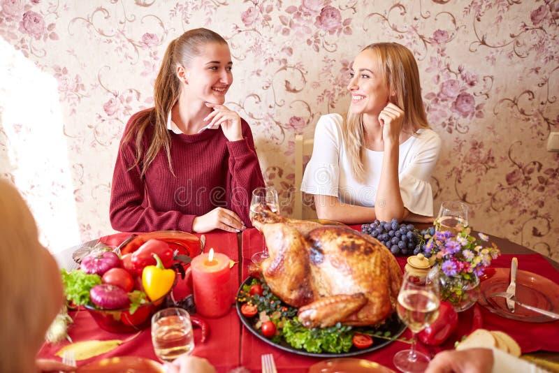 Hermanas felices en la cena festiva de la acción de gracias de la familia en un fondo ligero Concepto de celebración nacional fotos de archivo
