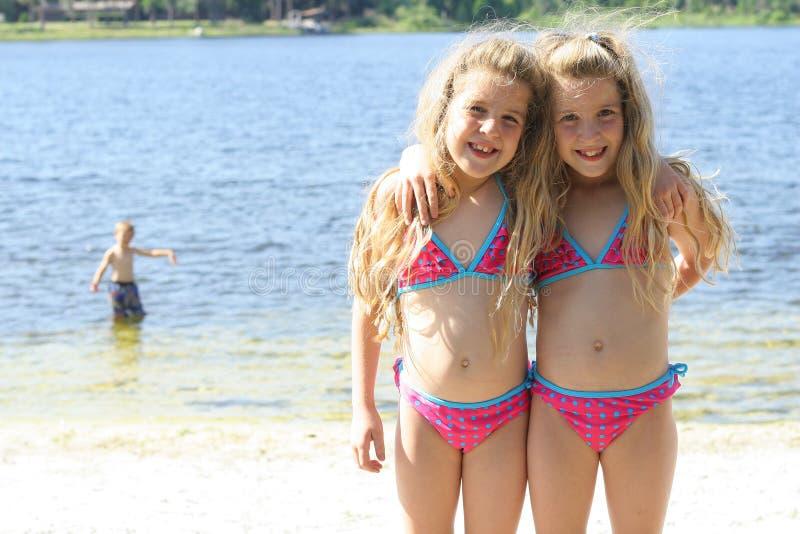 Hermanas gemelas en bañadores en el lago foto de archivo