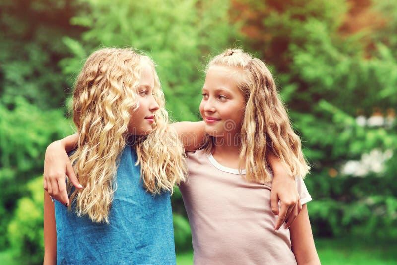 Hermanas gemelas felices abrazándose afuera Caminata familiar en el parque de verano Muchachas felices paseando en la naturaleza foto de archivo libre de regalías