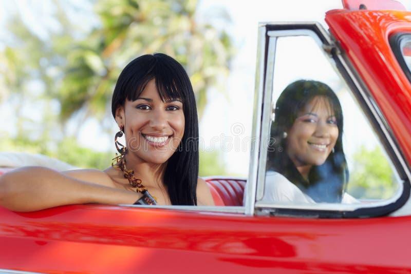 Hermanas gemelas hermosas en coche del cabriolé imagen de archivo libre de regalías