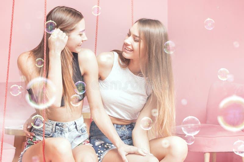 Hermanas hermosas de los gemelos que sonríen junto, momentos felices fotografía de archivo