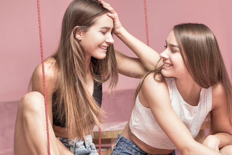 Hermanas hermosas de los gemelos que sonríen junto, momentos felices imagen de archivo