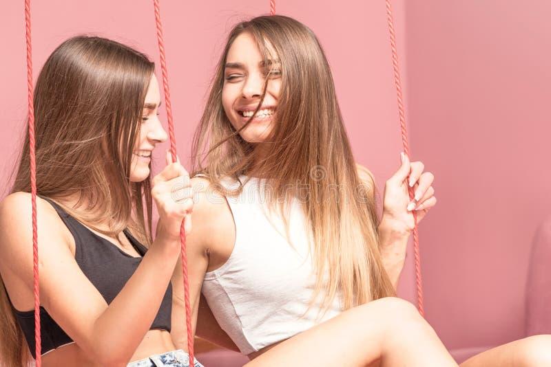 Hermanas hermosas de los gemelos que sonríen junto, momentos felices fotos de archivo