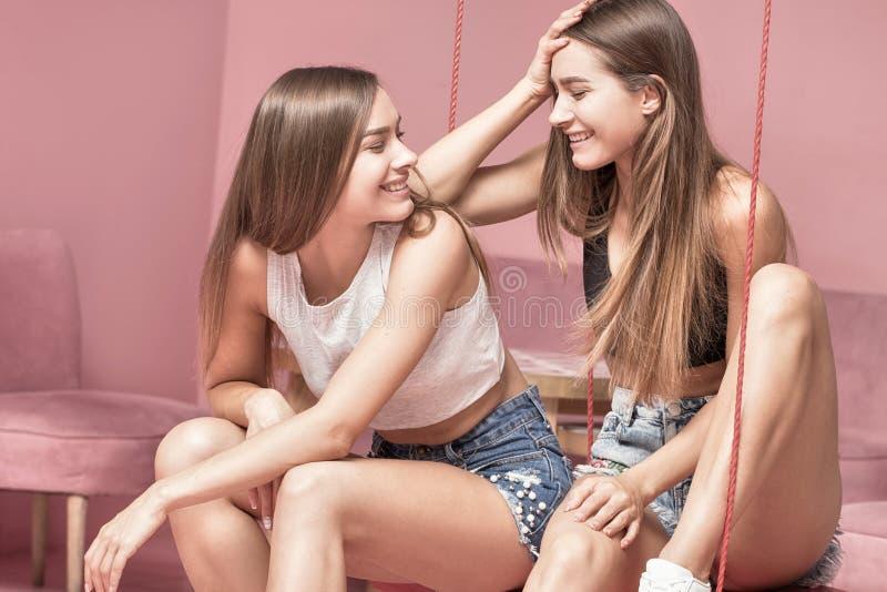 Hermanas hermosas de los gemelos que sonríen junto, momentos felices imagenes de archivo