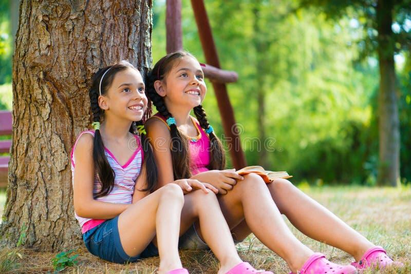 Hermanas hispánicas que se sientan bajo el árbol y hablar imagenes de archivo
