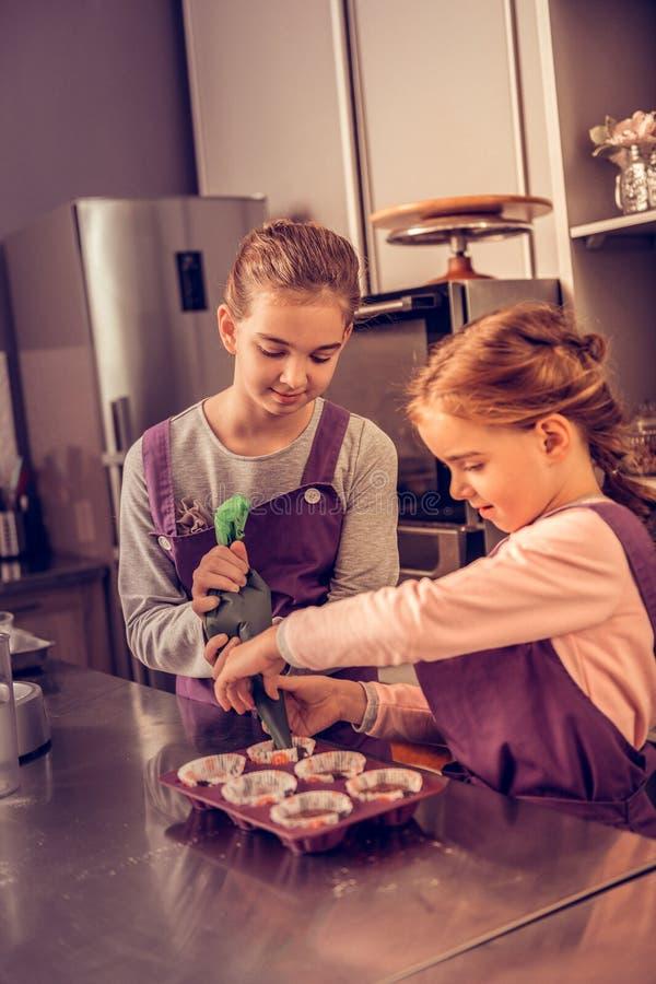 Hermanas jovenes agradables alegres que preparan los molletes juntos fotos de archivo
