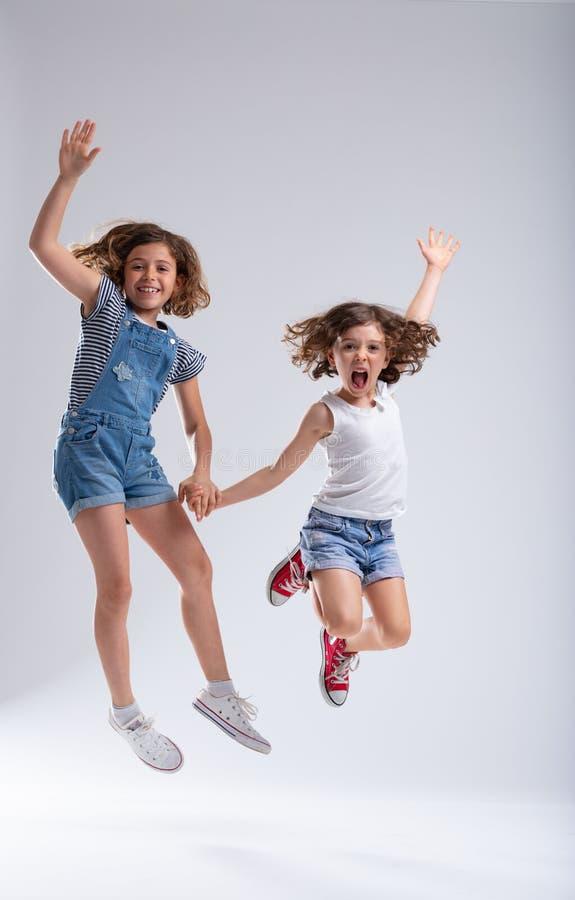 Hermanas jovenes exuberantes que saltan para la alegría imagenes de archivo