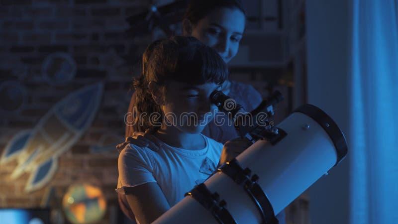 Hermanas lindas que miran las estrellas con un telescopio imágenes de archivo libres de regalías