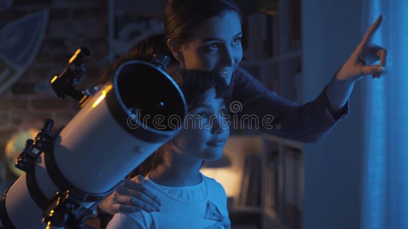 Hermanas lindas que miran las estrellas con un telescopio fotografía de archivo