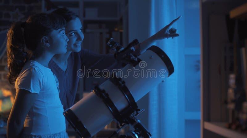 Hermanas lindas que miran las estrellas con un telescopio fotografía de archivo libre de regalías