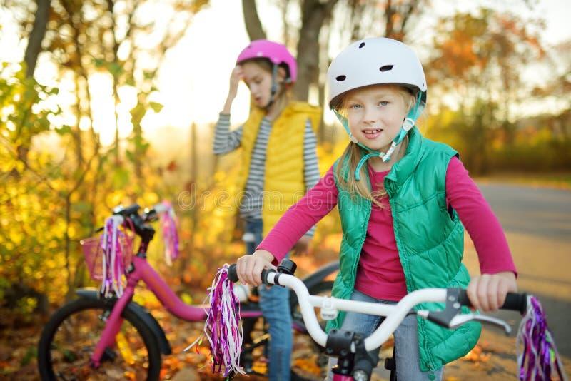 Hermanas lindas que montan las bicis en un parque de la ciudad en día soleado del otoño Ocio activo de la familia con los niños N fotografía de archivo