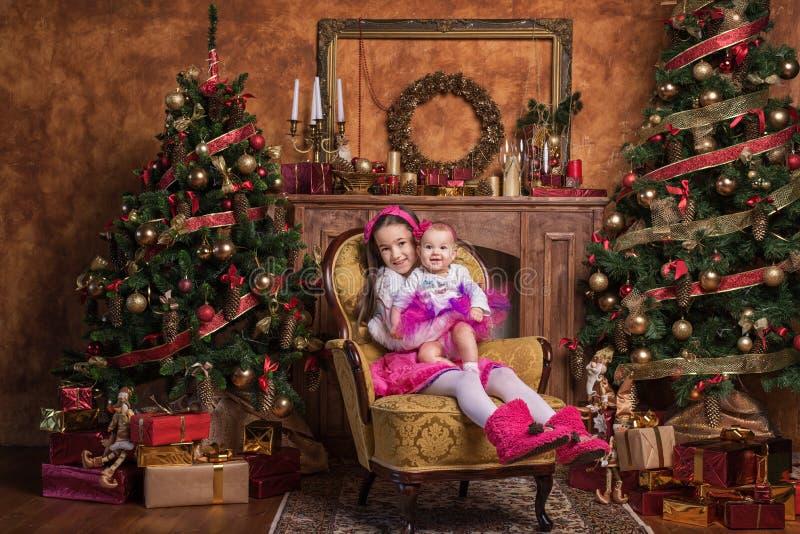 Hermanas lindas que se sientan cerca de los árboles de navidad foto de archivo