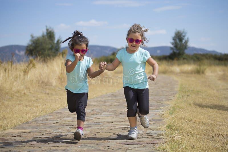 Hermanas preciosas que corren a lo largo de la trayectoria en campo imágenes de archivo libres de regalías
