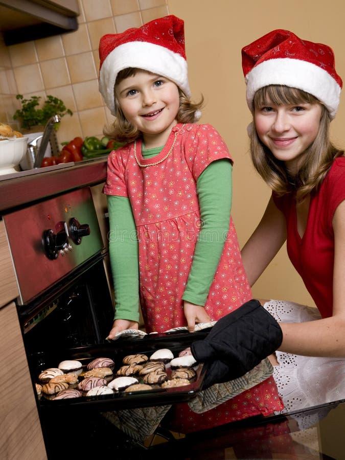 Hermanas que cuecen al horno las galletas de la Navidad imágenes de archivo libres de regalías