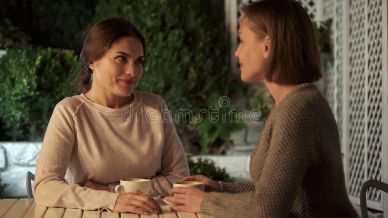 Hermanas que discuten las noticias agradables que se miran, tiempo junto, amistad imagen de archivo