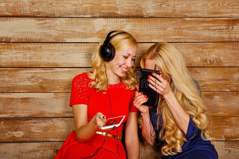 Hermanas que escuchan la música en los auriculares foto de archivo libre de regalías