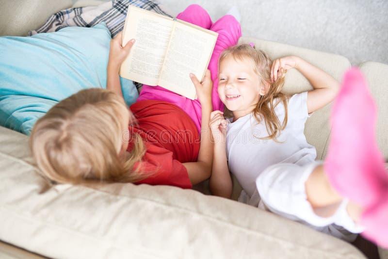 Hermanas que leen cuentos de hadas fotos de archivo libres de regalías