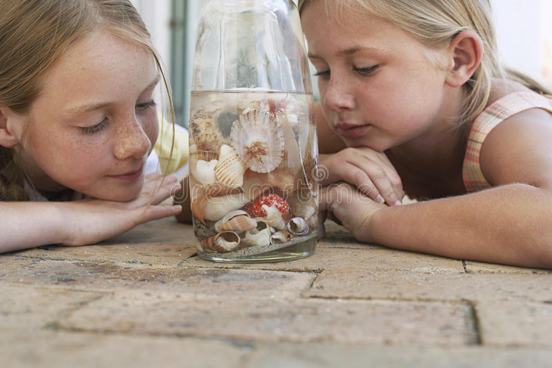 Hermanas que miran conchas marinas en botella fotografía de archivo
