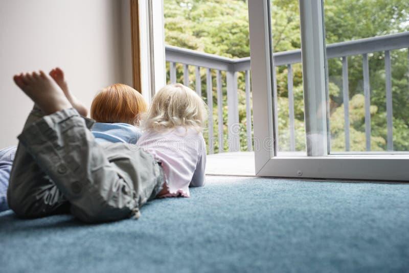 Hermanas que miran a través de balcón mientras que miente en la alfombra fotos de archivo