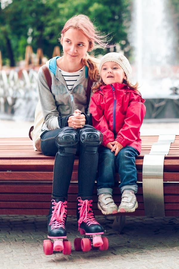 Hermanas que se sientan en banco fotografía de archivo libre de regalías