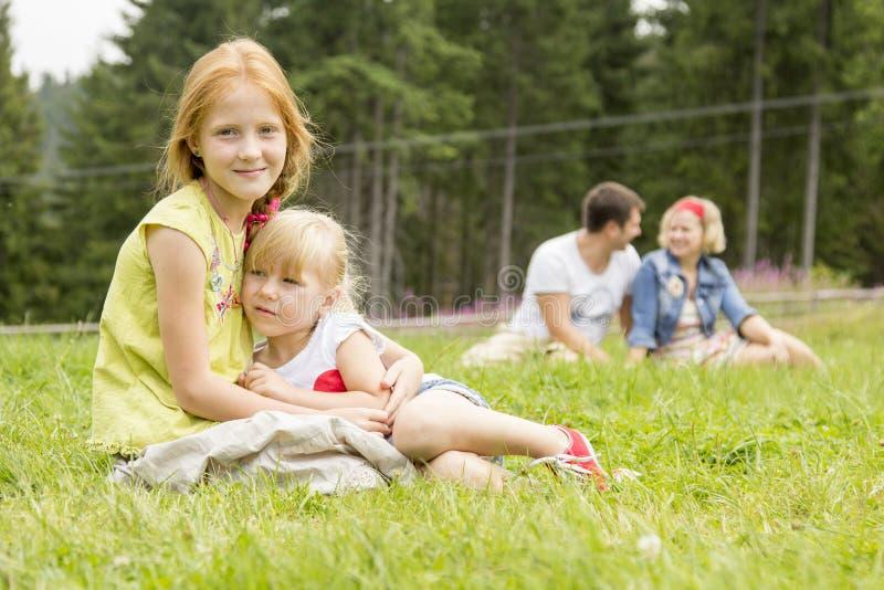 Hermanas que se sientan en el prado imagen de archivo