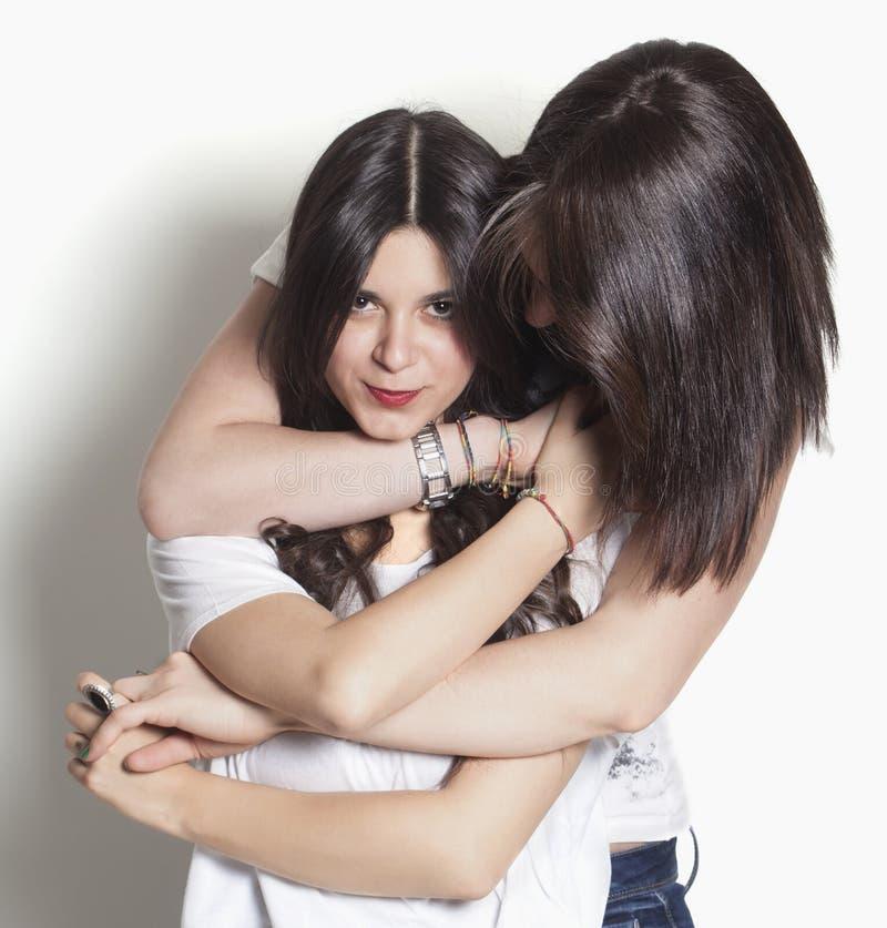 Hermanas que sonríen y que abrazan imagen de archivo