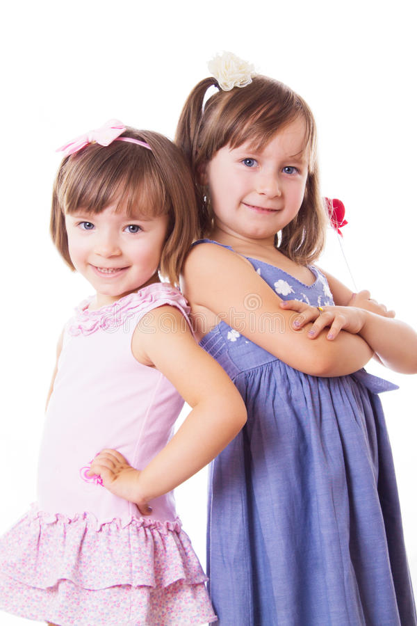 Hermanas sonrientes que se colocan con su parte posterior fotografía de archivo