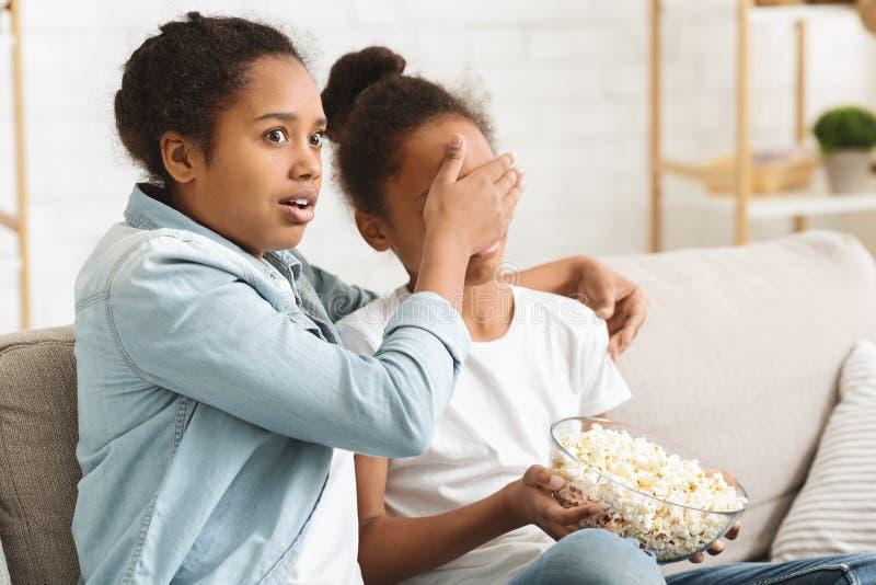 Hermanas viendo el horror en la televisión en casa durante el día fotos de archivo libres de regalías