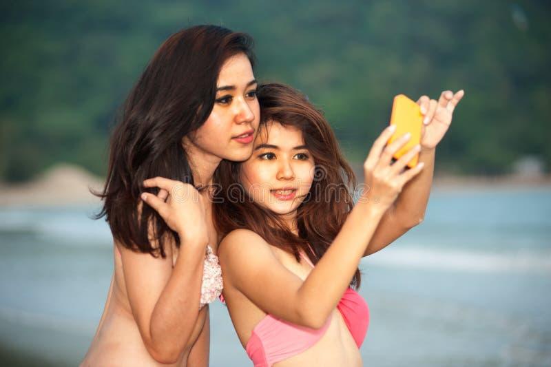 Hermane a la mujer bastante tailandesa alegre con el teléfono celular en la playa. fotografía de archivo