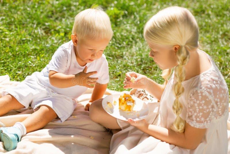 Hermano agradable y hermana que comen los dulces sabrosos fotografía de archivo libre de regalías