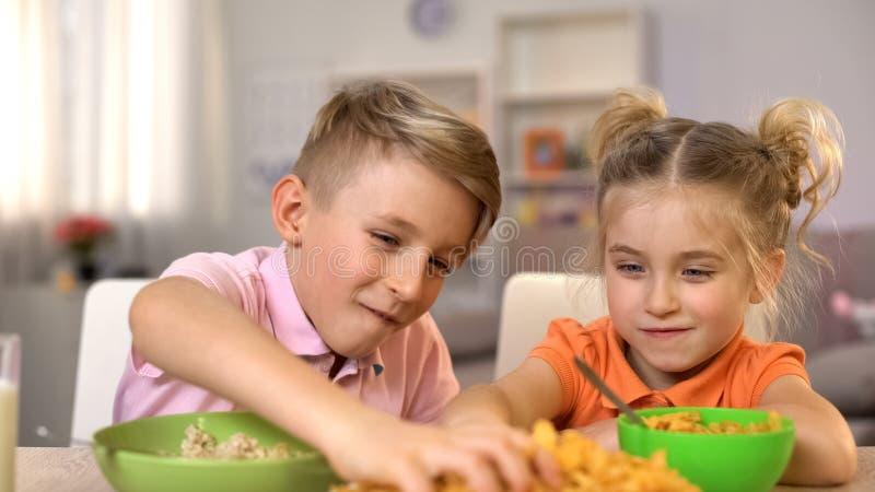 Hermano alegre y hermana que se divierten con la comida, niñez feliz, bromistas foto de archivo