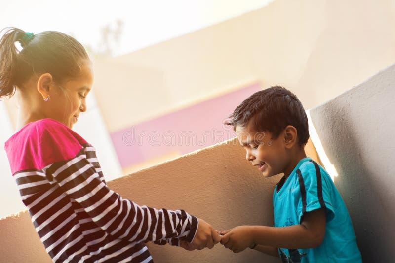 Hermano de dos niños indio y hermana o hermanos que luchan para el teléfono móvil en al aire libre fotos de archivo libres de regalías