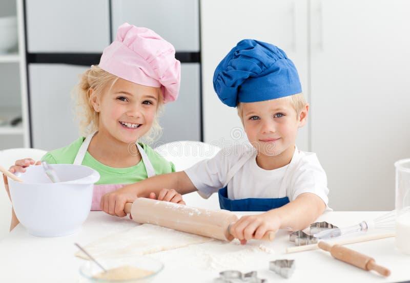 Hermano feliz y hermana que preparan una pasta imagenes de archivo