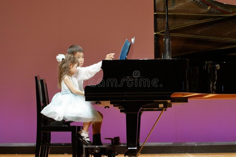 Hermano japonés y hermana que juegan el piano en etapa fotos de archivo