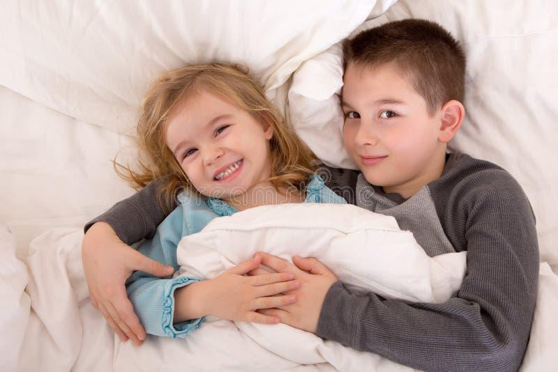 Hermano joven y hermana dañosos en cama imágenes de archivo libres de regalías