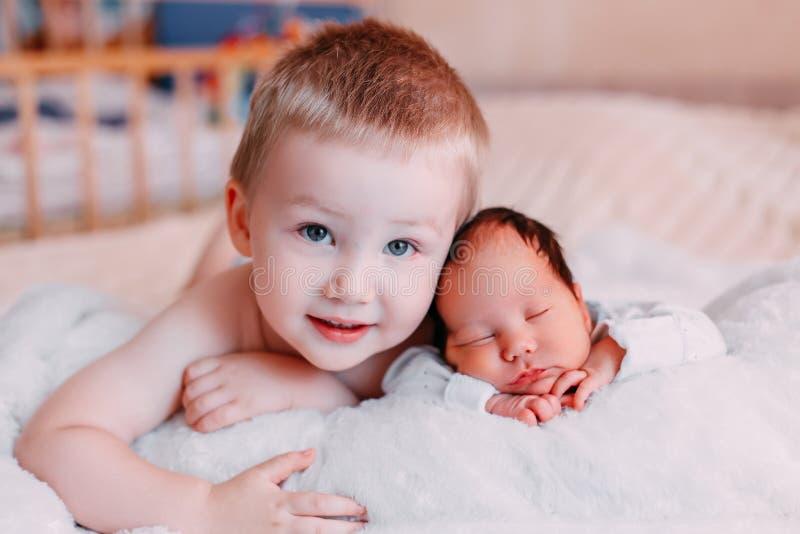 Hermano mayor y hermana recién nacida del bebé que mienten en cama en casa fotos de archivo libres de regalías