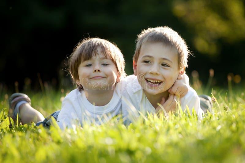 Hermano y hermana en hierba fotografía de archivo