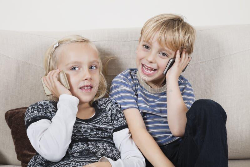 Hermano y hermana felices que usa los teléfonos celulares en casa fotografía de archivo libre de regalías