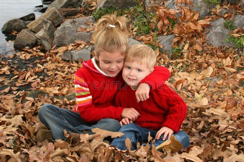 Hermano y hermana que abrazan en el parque imagenes de archivo