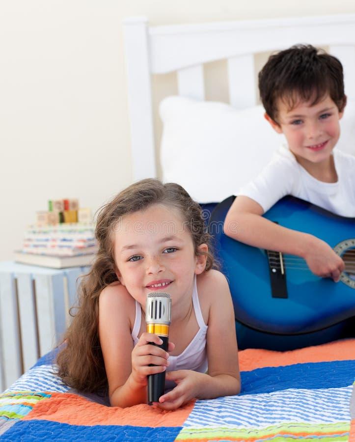 Hermano y hermana que cantan y que tocan la guitarra imagen de archivo